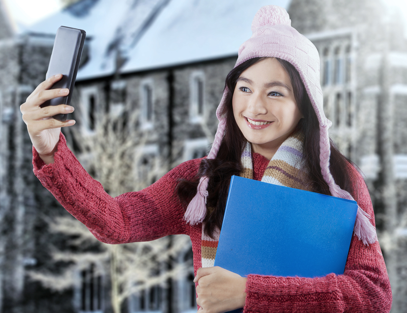 http://www.dreamstime.com/stock-image-sweet-student-winter-clothes-taking-picture-young-asian-girl-holding-folder-wearing-sweater-self-portrait-outdoors-image46599251
